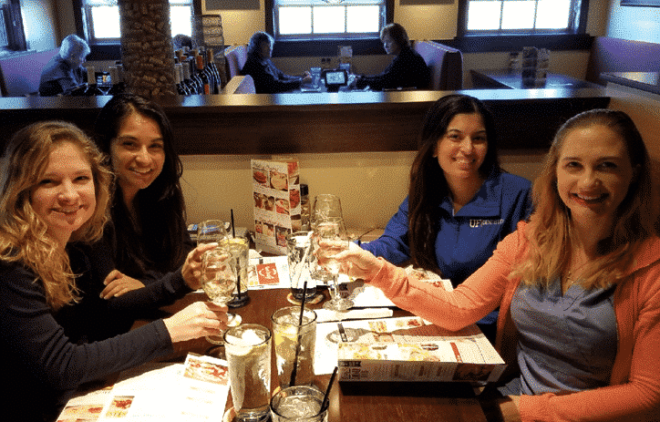 Four young women celebrating their  River Oak healthy smiles at a restaurant