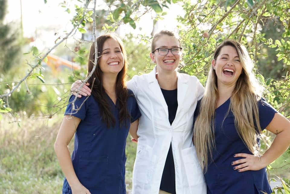 Three smiling dentists pose for a picture in nature in Palm Bay FL.