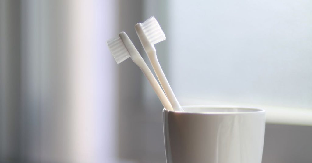 Two toothbrushes in a cup at River Oak Dental in Palm Bay Fl.