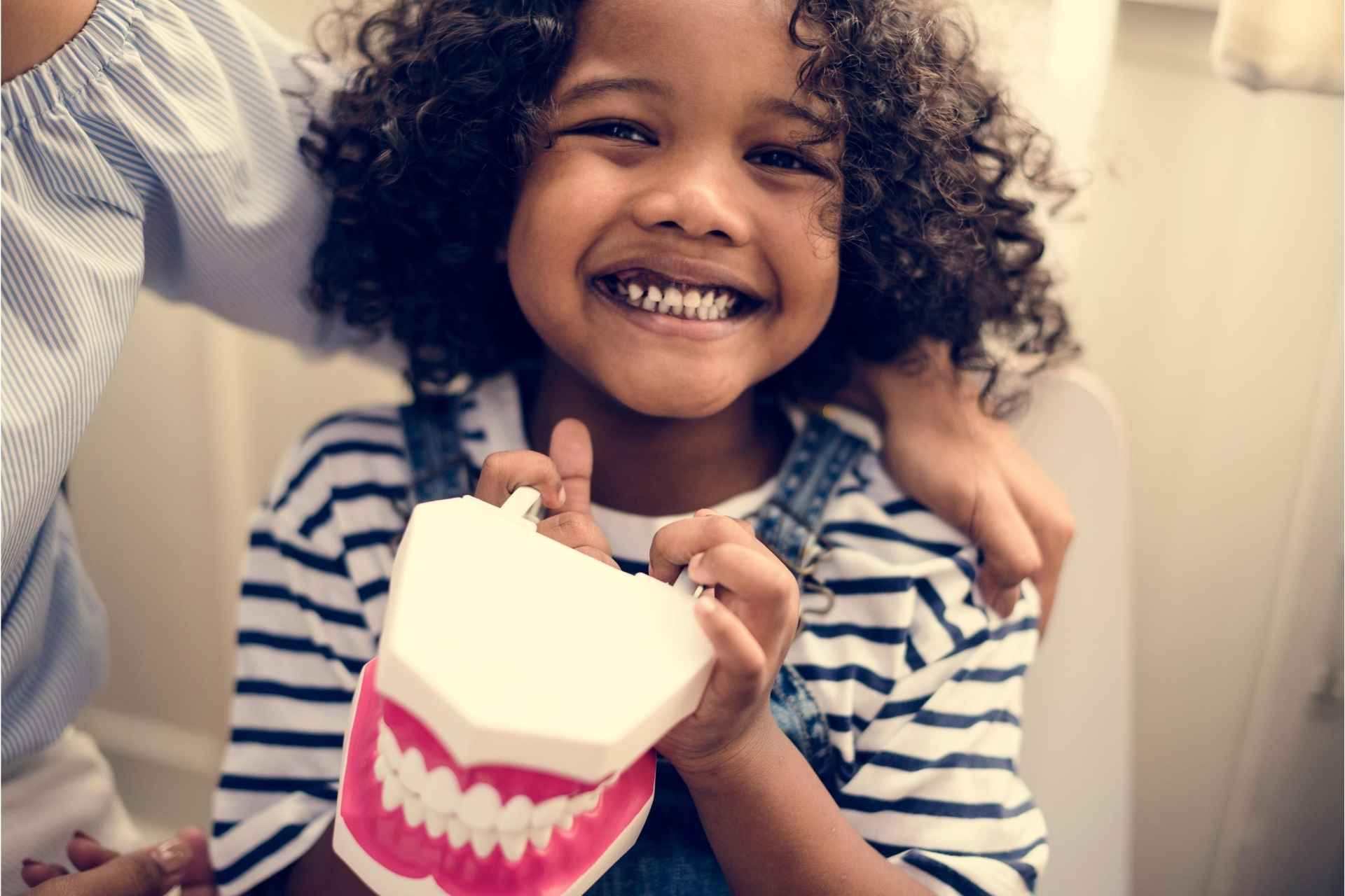Little girl holding dentures