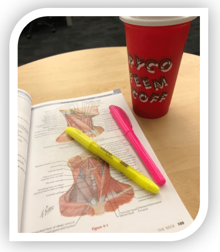 Book with human anatomy and cup of coffee